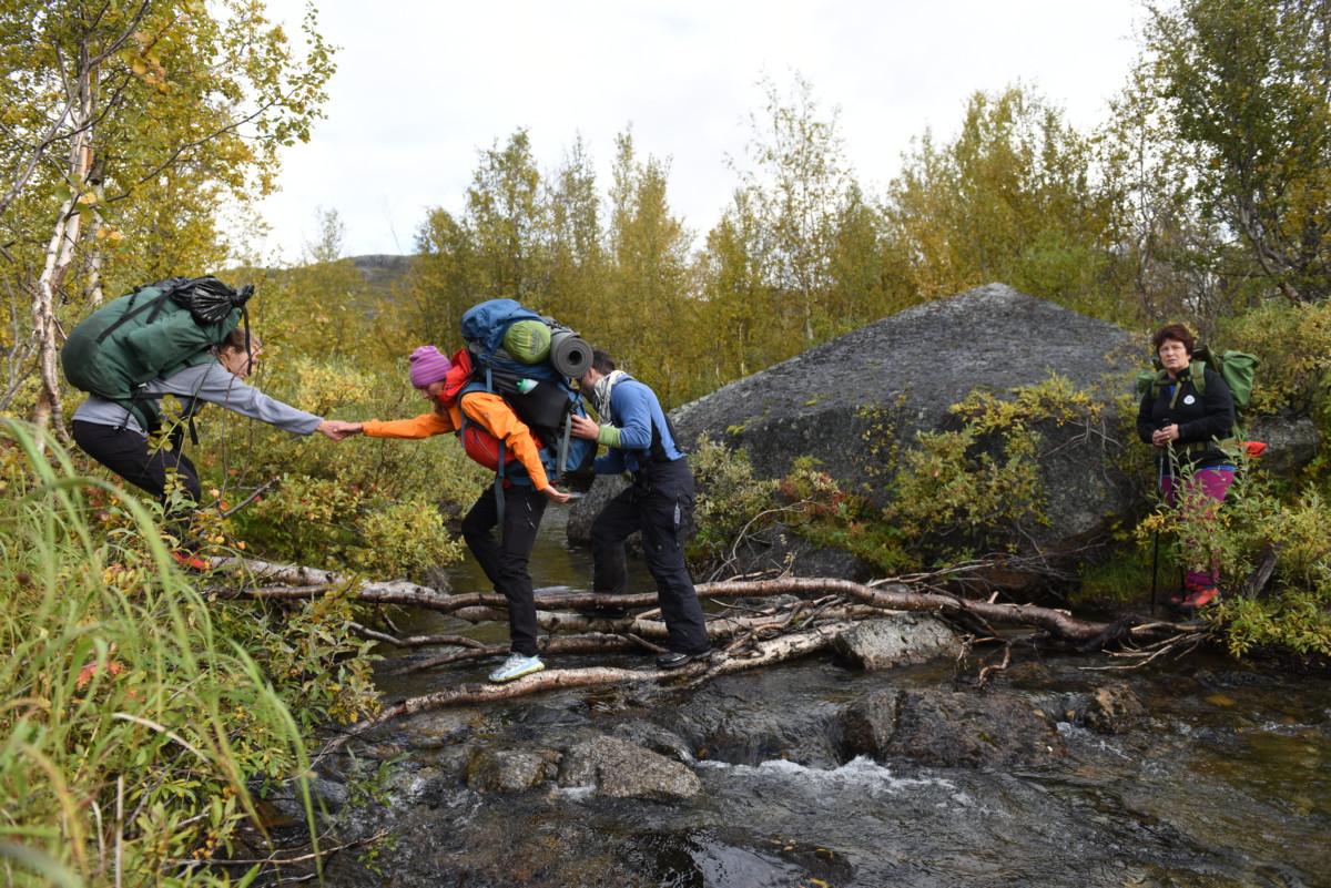 Andre og Kim Marius hjelper Elin trygt over elven.